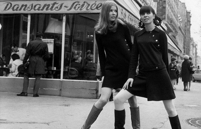 photo des années 60 en noir et blanc montrant deux jeunes femmes habillées en robe mini noires et bottes, publiée dans le magazine les boomeuses.com