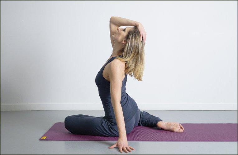 Photo de Femme en train de faire des mouvements de gym sur un tapis au sol publiée dans les boomeuses.com