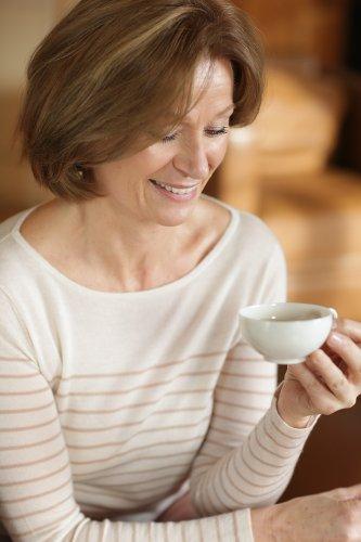 Femme d'une cinquantaine d'année souriante en train de boire du thé, publiée dans le magazine les Boomeuses