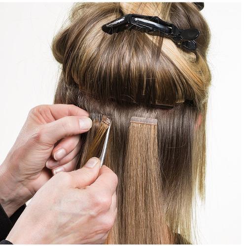 Coiffeur en train de fixer des extensions sur les cheveux d'une femme