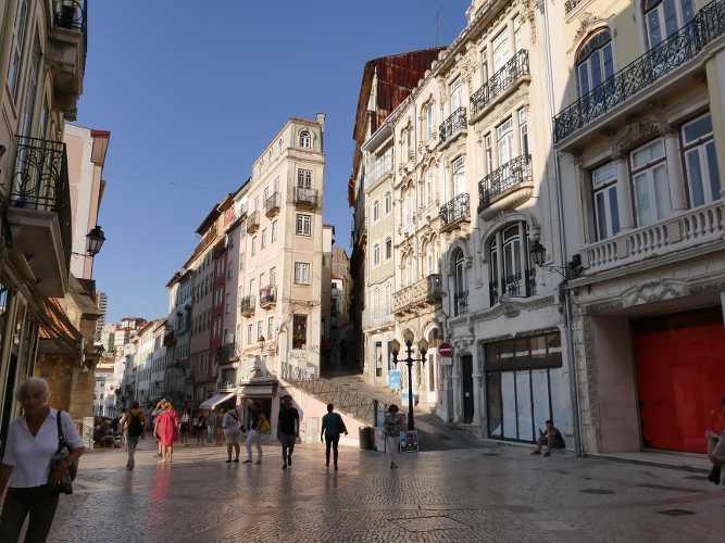 photo de rue avec immeuble et passants à Coimbra