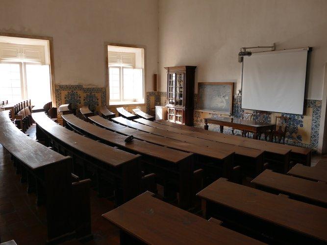 photo d'une salle de l'université de Coimbra au portugal avec des bancs anciens anciens