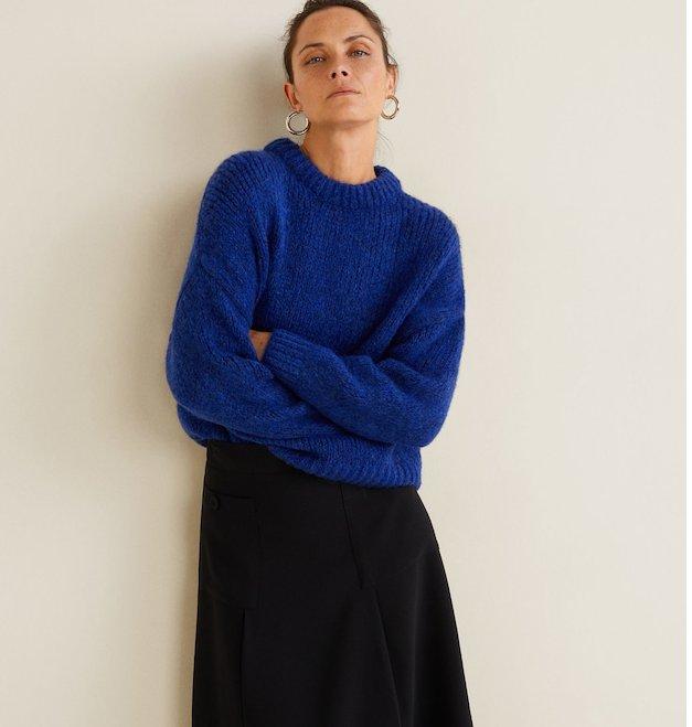 femme adossée à un mur avec une jupe évasée noire et un gros pull bleu en laine