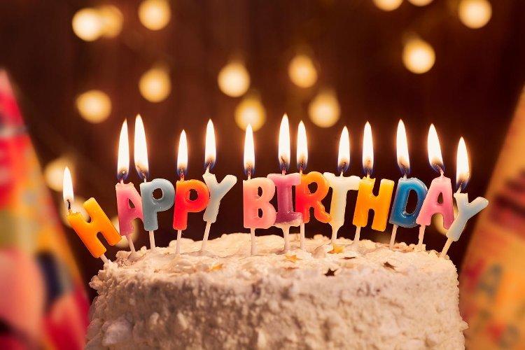 photo représentant un gâteau d'anniversaire avec des bougies marquées Happy Birthday allumées