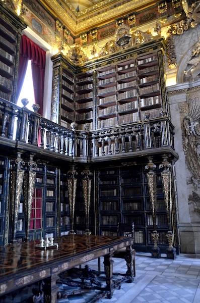 photo représentant la bibliothèque de l'universté de Coimbra, Portugal, remplis de livres très anciennes