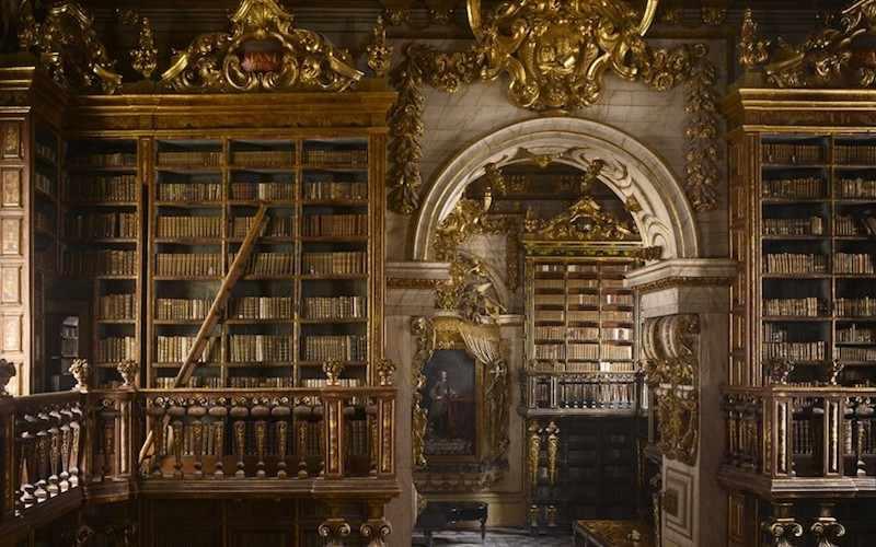 photo représentant la bibliothèque de l'universté de Coimbra, au portugal, remplis de livres très anciens