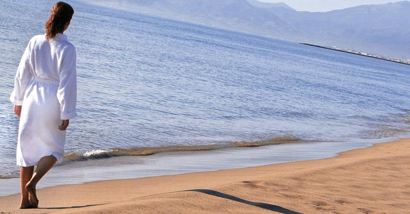 Femme en peignoir marchant sur une plage, article aptu dans le magazine les Boomeuses