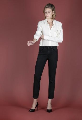 femme portant un jean droit et une chemise blanche