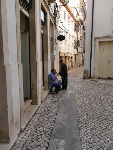 deux hommes parlant dans une ruelle au Portugal