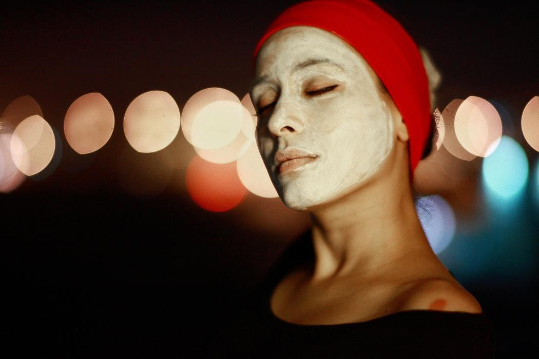Photo d'une femmeavec un bandeau rouge dans les cheveux et les yeux fermés, recouverte d'un masque pour la peau