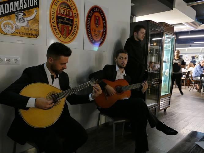deux hommes jouant de la guitare dans un restaurant au portugal