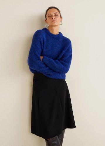 femme adossé à un mur portant un pull en line bleu et une jupe noire évasée