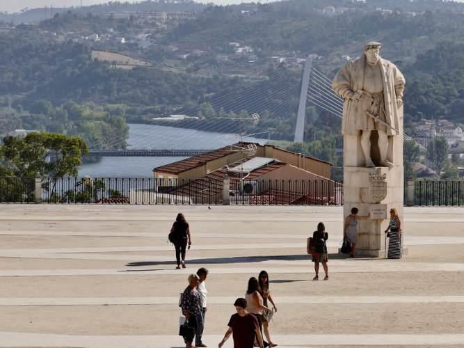 Place avec un statue en pierre devant le fleuve de la ville de Coimbra au Portugal