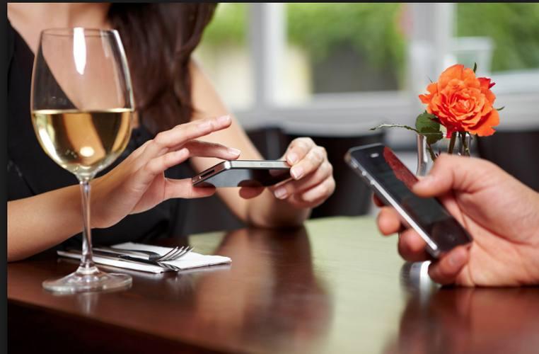Couple au restaurant regardant chacun son portable, paru dans le magazine les Boomeuses
