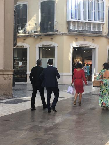 Photo de deux hommes en costume noir et deux femmes en robes chics marchant dans une rue, publiée dans le magazine Les boomeuses