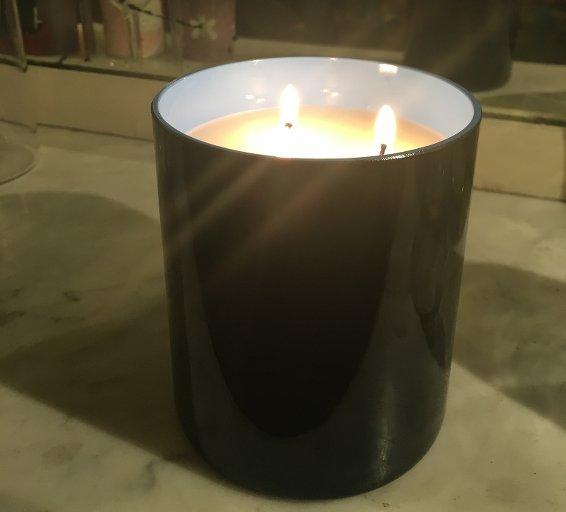 bougie parfumée allumée posée sur une cheminée, paruedans le magazine Les Boomeuses