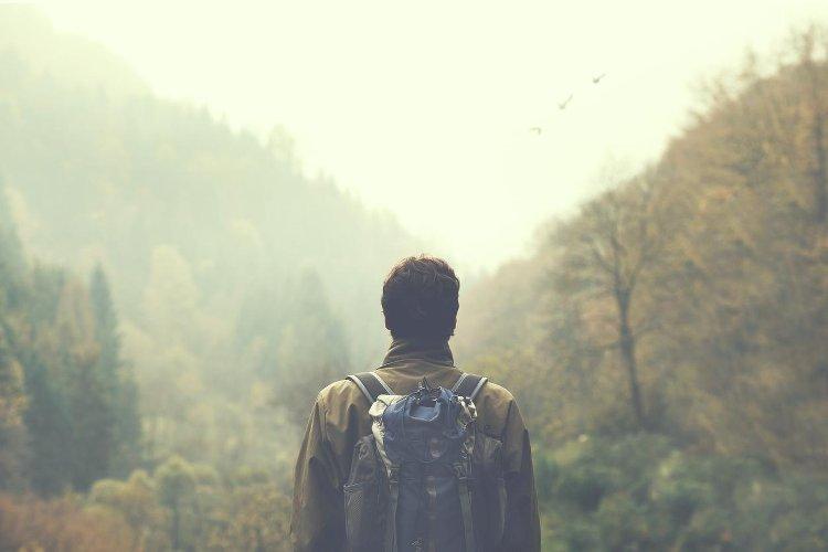 Photo montrant un homme marchant dans la forêt avec un sac à dos sur les épaules. Photo parue dans le magazine Les Boomeuses