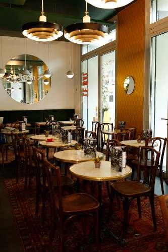 photo de l'intérieur d'un café avec des tables bistrots et des chaise sen bois, parue dans les boomeuses magazine