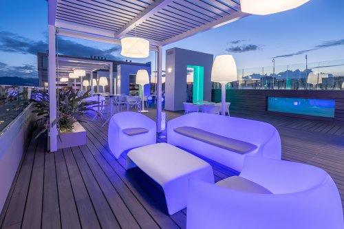 Photo de nuit de la terrasse d'un hôtel avec canapé et fauteuils blancs