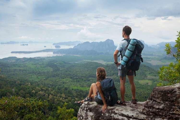 photo montrant un jeune couple voyageant, portant chacun un sac dos , photo parue dans les boomeuses magazine