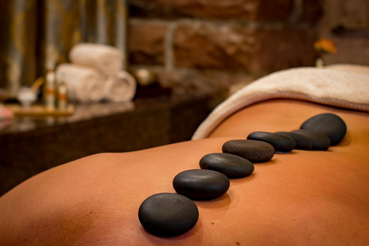 Photo d'une femme couché sur le ventre avec des pierres chaudes sur le dos publié, dans les boomeuses magazine