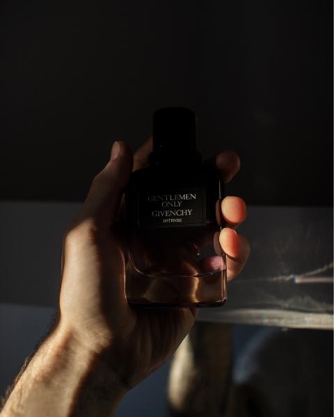 main d'homme tenant un flacon de parfum sur les boomeuses