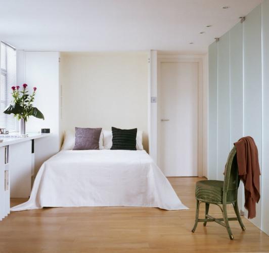 chambre avec un lit double recouvert d'un édredon blanc publiée dans le magazine les boomeuses
