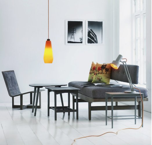 Photo d'un salon avec des meubles minimalistes gris et une suspension orange, les boomeuses