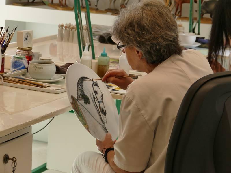 femme au Portugal en train de peindre un motif de cheval sur une assiette en porcelaine, publiée dans les boomeuses