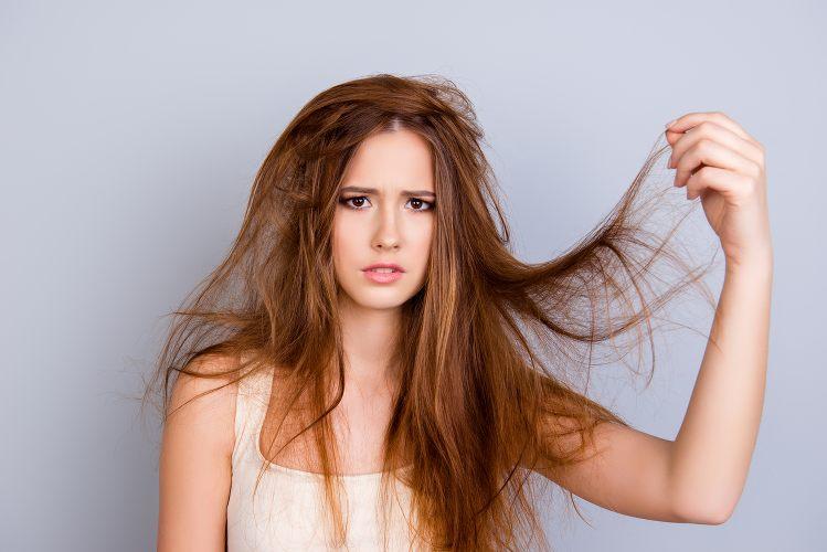 Jeune femme aux cheveux longs les prenant dans une de ses mains et faisant la grimace