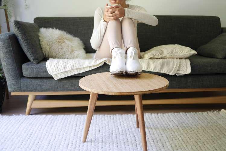 Photo d'une femme assise sur son canapé portant des chaussons blancs posés, sur une table basse, parue dans le magazine les boomeuses