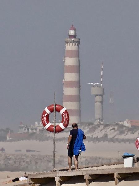personne au bord de la plage avec au fond un phare rouge et blanc, les boomeuses