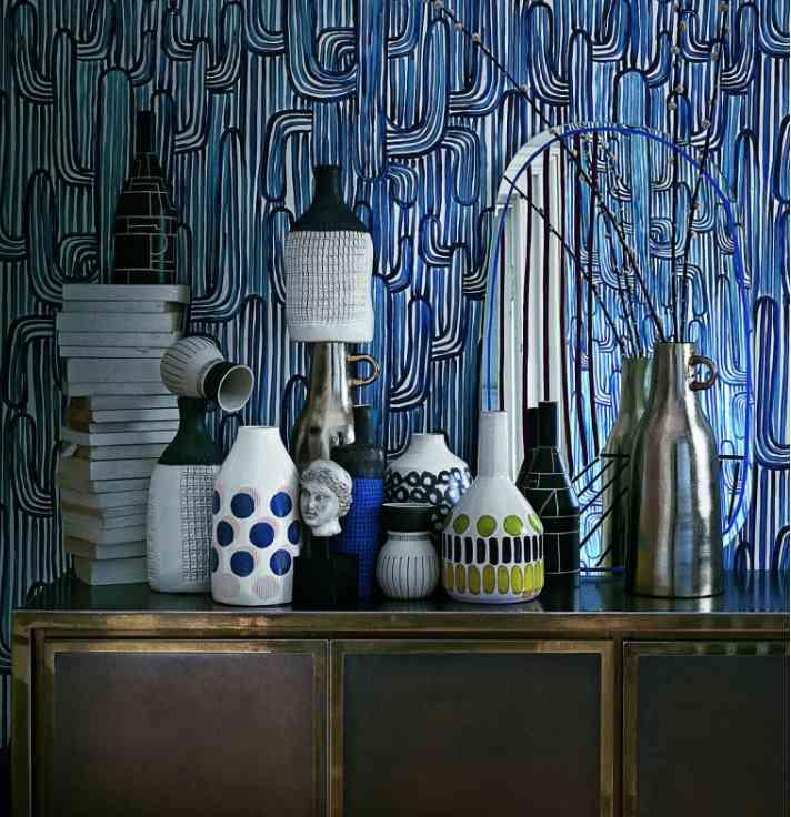 photo d'une pièce avec papier peint bleu au mur et des bibelots sur une commode, les boomeuses