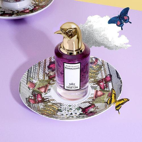 Parfum violet avec bec de canard doré en capuchon posé sur une soucoupe fleurie, les boomeuses