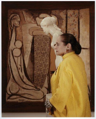 Helena Rubisntein photographiée avec un manteau jaune devant un tableau publiée dans le magazine les boomeuses