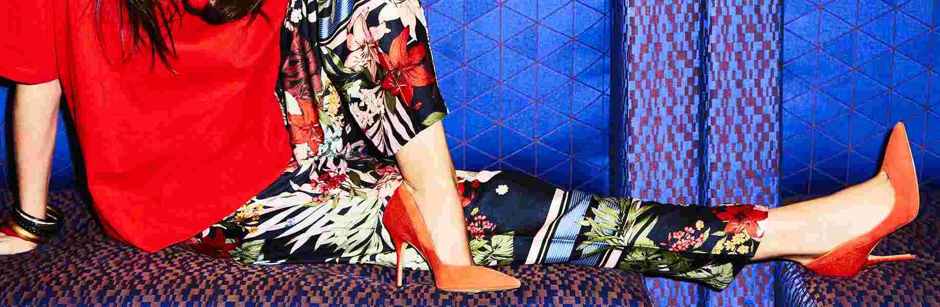 photo d'une femme assise par terre avec un pantalon fleuri et des chaussures à talon rouges, les boomeuses