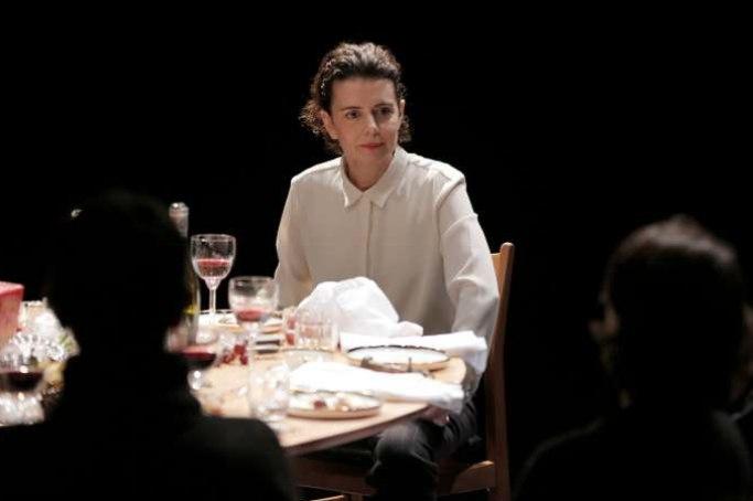 photo de la pièce Girls and boys, avec une femme en chemise blanche assise devant une table avec les restes d'un dîner, paru dans le magazine les boomeuses.com