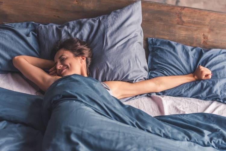 choisir une bonne literie. photo d'une femme dans un lit en train de s'étirer publié dans les boomeuses