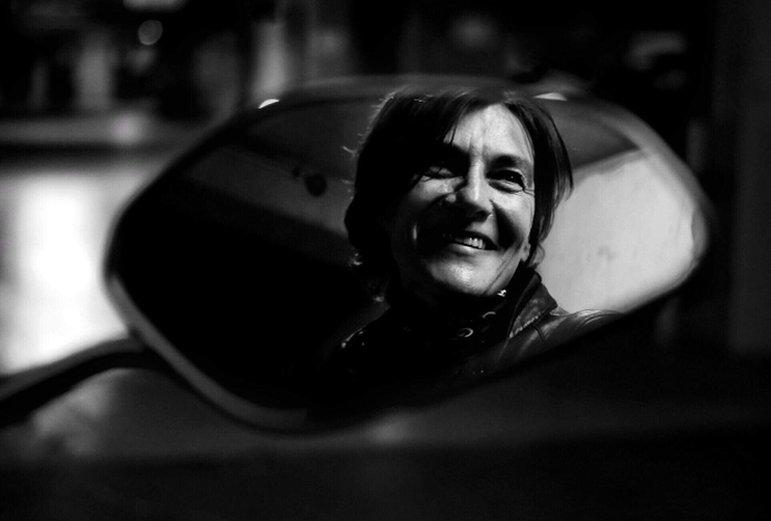 portrait de femme en noir et blanc assise sur sa moto