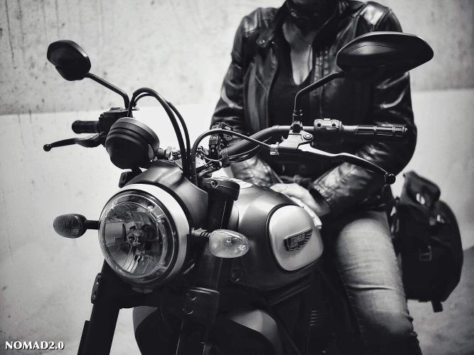 femme dont on bvoit pas la tête assise sur sa moto