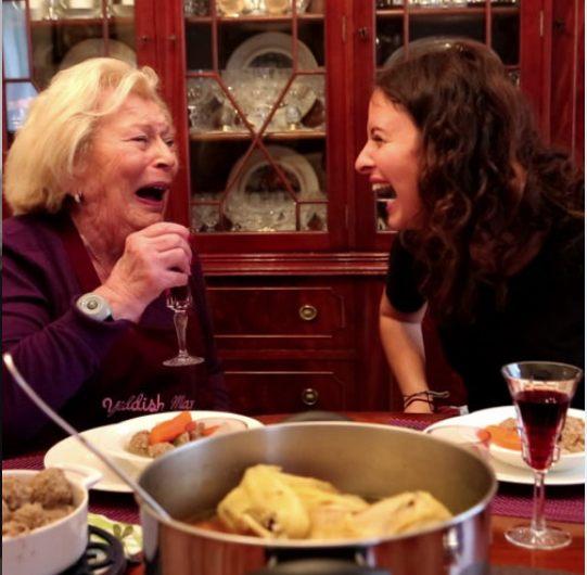 grand-mère et sa petite fille en train de rire autour d'une table avec de la cuisine