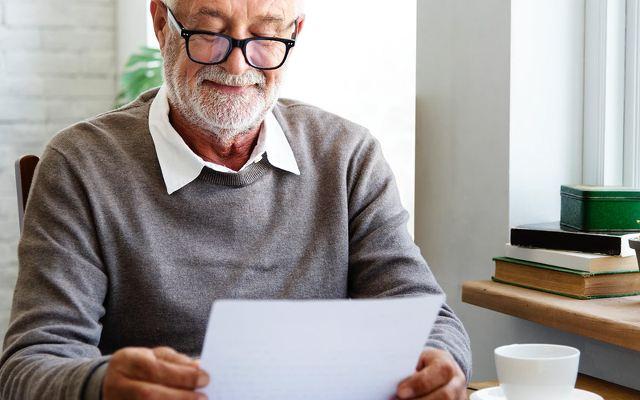 homme barbu avec lunette en train de relire sa biographie