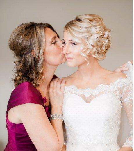 mère d'une mariée embrassant sa fille en robe de mariée