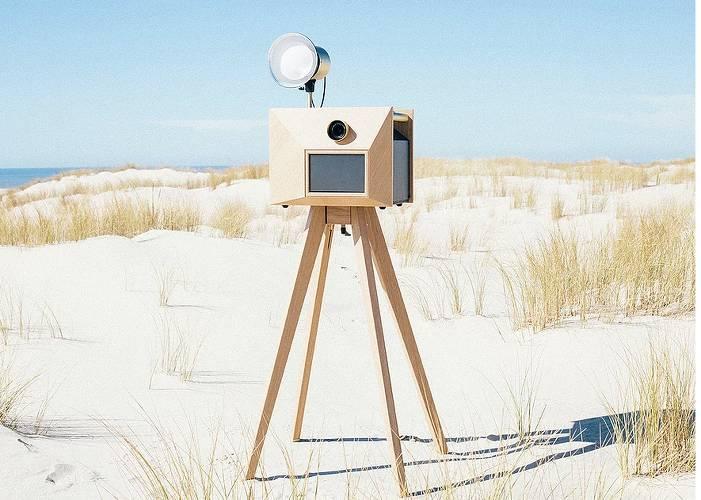 appareil de photo en bois sur pied posée sur le sable pour photos de mariage