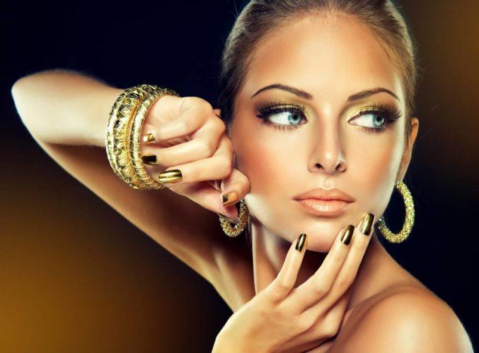 femme portant des boucles d'oreile en or et des bracelets joncs en or