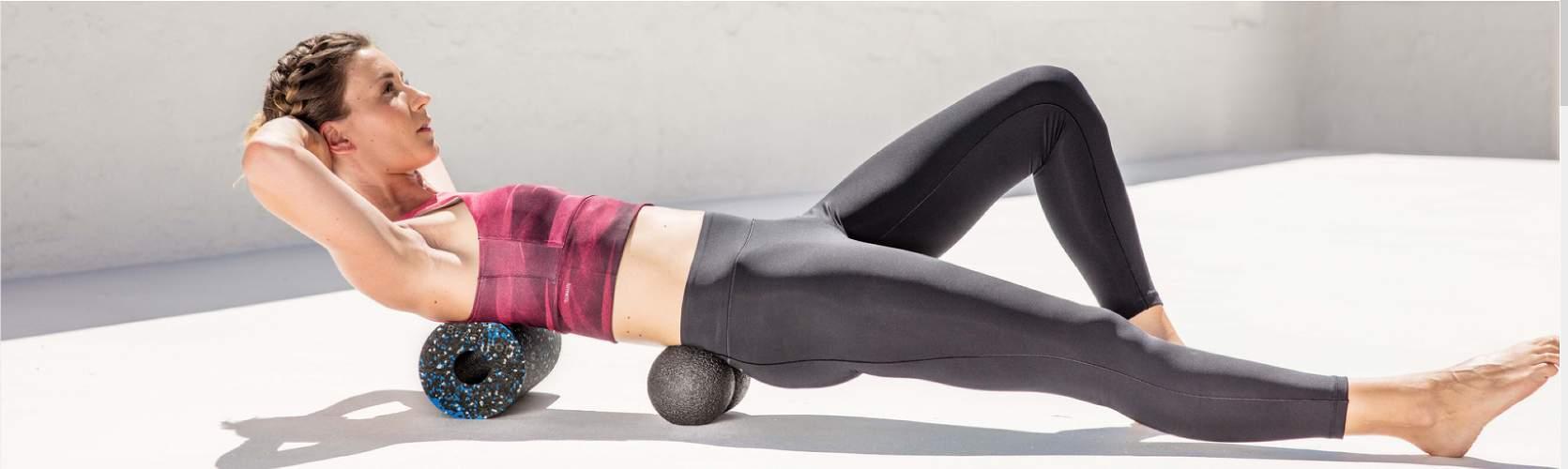 femme en train de faire du sport sur des rouleaux d'automassage