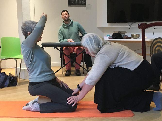 femmes en train de presser les genoux d'une femme à genoux lors d'un stage sur la voix