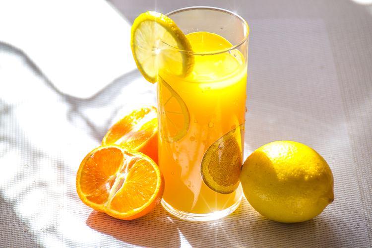 verre de jus d'orange et citrons à côté