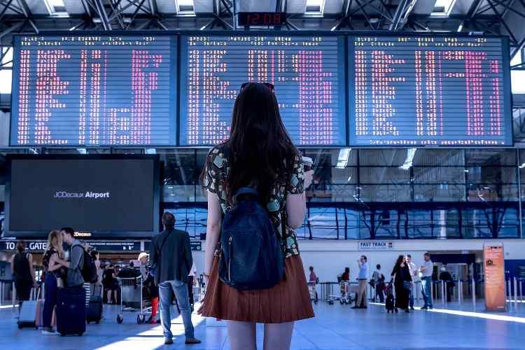 femme devant l'affichage des avions retardés
